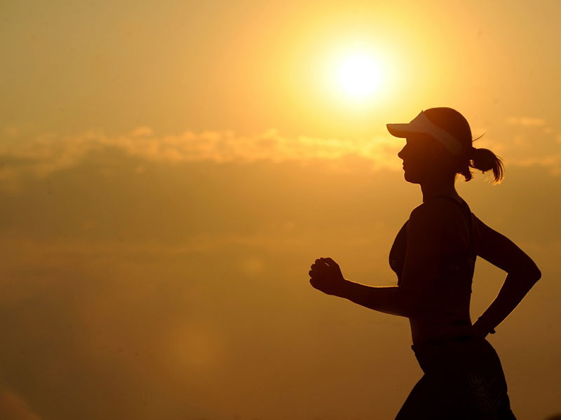 Exercise category image of a silhouette of a woman running with background stunning orange sunset