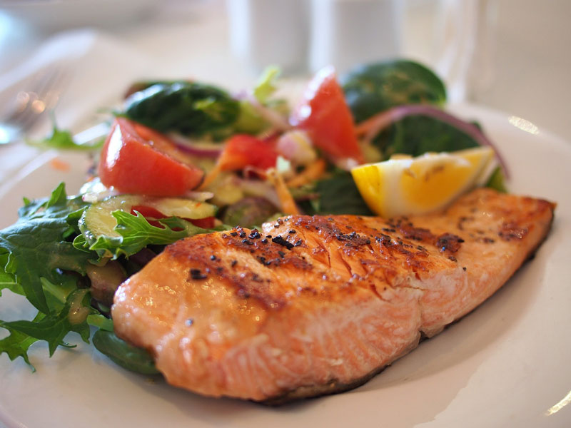 Food category image of a plate of cooked salmon with a dressed salad and wedge of lemon