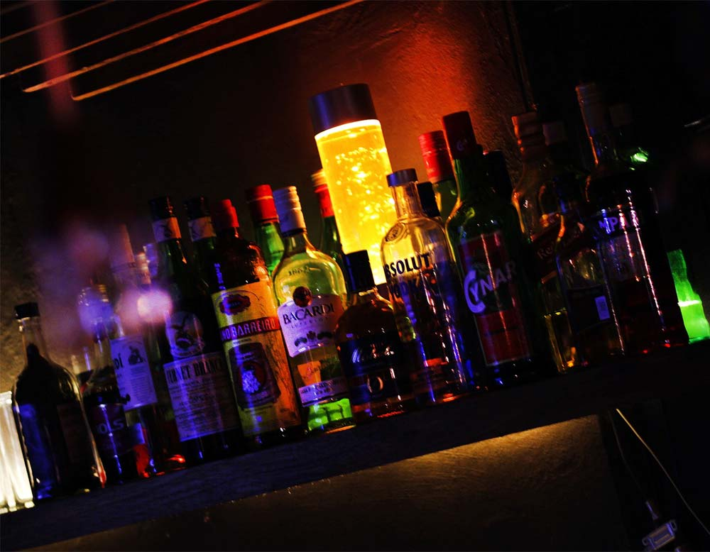 Alcohol Awareness image of lots of bottles of different alcohol on a shelf in a bar at night