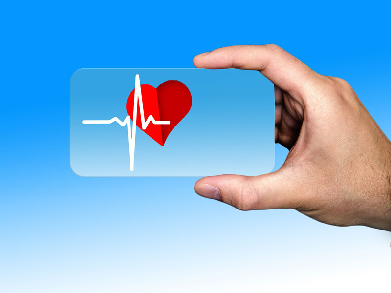 cardiovascular category image with a hand holding a landscape mobile shape piece of glass with a red heart and white pulse graph