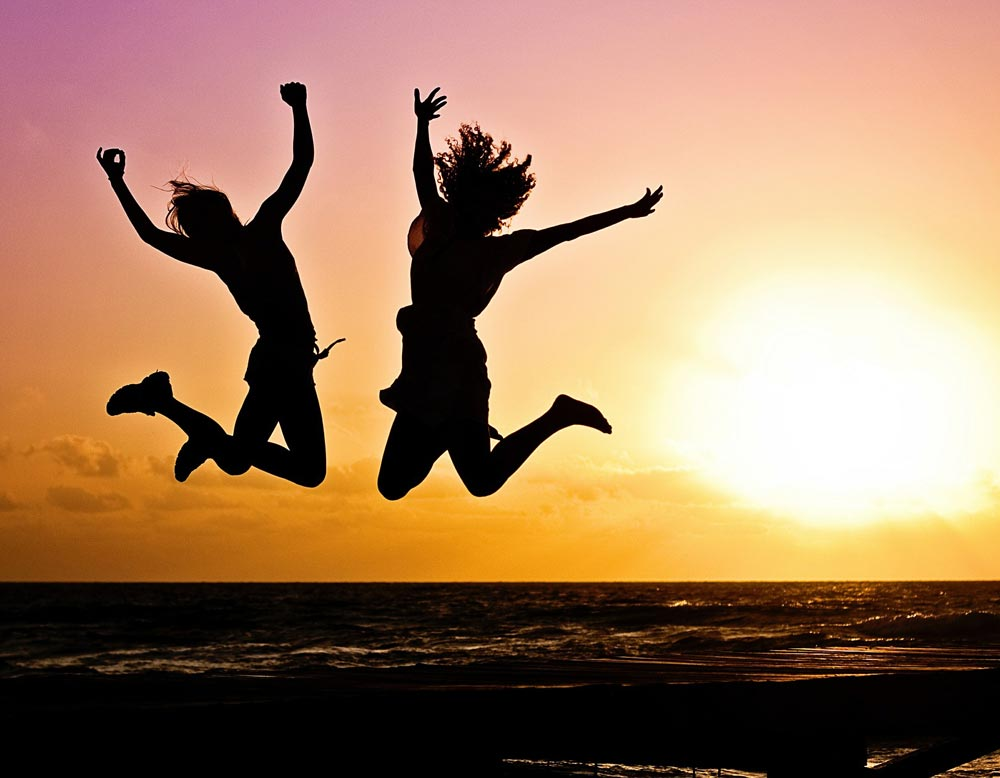 Exercise image of two people jumping silhouetted against a beautiful sunset in the background